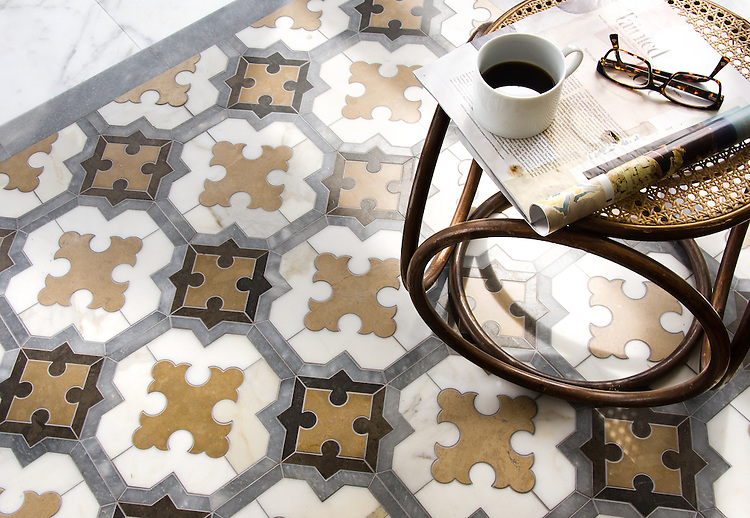 Corsini, a waterjet mosaic, shown in honed Calacatta Tia, Cavern, Lagos Gold, and Allure, is part of the Miraflores collection by Paul Schatz for New Ravenna.