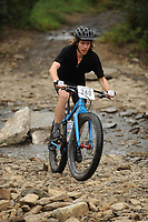 NWA Democrat-Gazette/ANDY SHUPE<br /> Chandler Armstrong of Champaign, Ill., rides across Lee Creek Saturday, Sept. 19, 2015, during the Northwest Arkansas Mountain Bike Championships at Devil's Den State park.