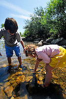 Young boy and girl playing in shallows of Yampa River, Steamboat Springs, Colorado