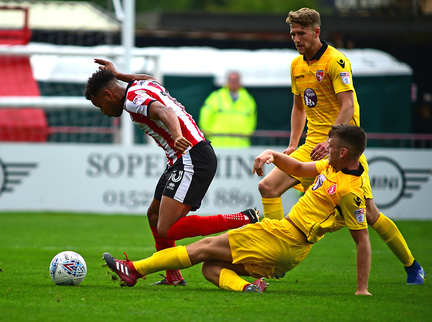 Lincoln City's Matt Green avoids the challenge of Morecambe's Sam Lavelle to equalise<br /> <br /> Photographer Andrew Vaughan/CameraSport<br /> <br /> The EFL Sky Bet League Two - Lincoln City v Morecambe - Saturday August 12th 2017 - Sincil Bank - Lincoln<br /> <br /> World Copyright &copy; 2017 CameraSport. All rights reserved. 43 Linden Ave. Countesthorpe. Leicester. England. LE8 5PG - Tel: +44 (0) 116 277 4147 - admin@camerasport.com - www.camerasport.com