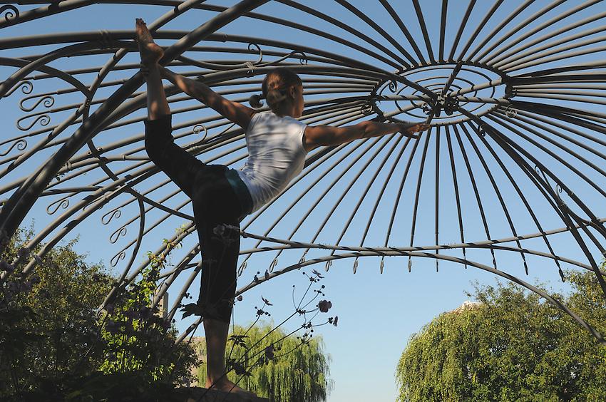 A beautiful young woman practicing yoga at Toronto Music Gardens