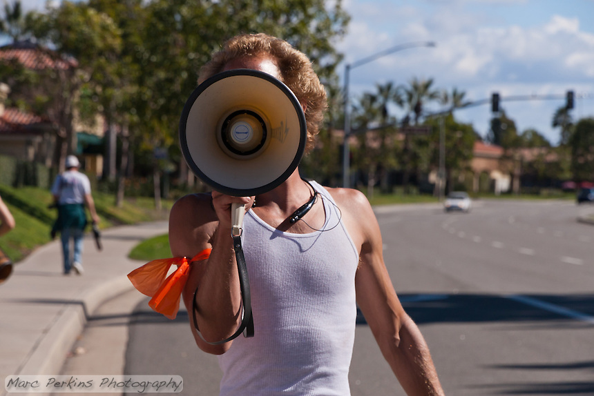 """""""Web"""" (Andrew), one of the leaders of the march, talks into a megaphone during the Occupy Orange County, Irvine march on November 5.  His orange arm band signifies that he's part of the Occupy Orange County safety brigade, responsible for ensuring all marchers follow laws and managing traffic around the march."""