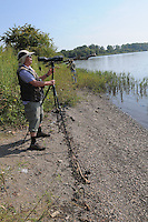 NWA Democrat-Gazette/FLIP PUTTHOFF <br /> Joe Neal sets up his spotting scope along the Arkansas River. A flock of pelicans were among the birds he saw on the water Sept. 16 2016 near Alma.