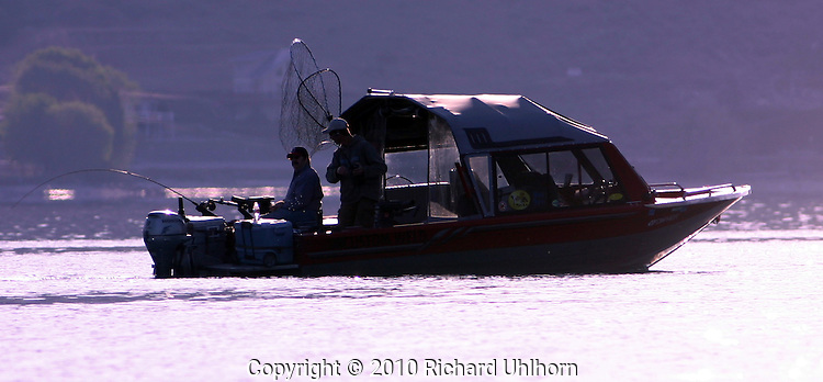 A fishing boat and fishermen try their luck on an early morrning outing on Lake Chelan in Washington State.
