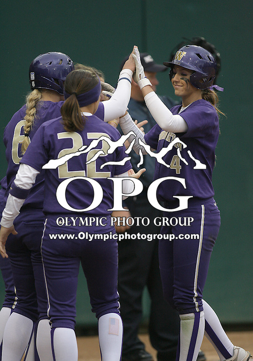 28 May 2010:  Washington Huskies players congratulate #4 Kimi Pohlman after she scored the games first run against Oklahoma.  Washington defeated Oklahoma 3-0 in the second game of the NCAA Super Regional at Husky Softball Stadium in Seattle, WA.
