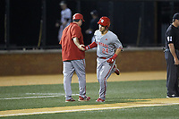 Luca Tresh (24) of the North Carolina State Wolfpack shakes hands with the third base couch after hitting a home run against the Wake Forest Demon Deacons at David F. Couch Ballpark on April 18, 2019 in  Winston-Salem, North Carolina. The Demon Deacons defeated the Wolfpack 7-3. (Brian Westerholt/Four Seam Images)