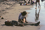 Girl Covering Guy On Beach With Sand And Mudd