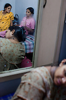 """In pink: Anjuman Salimkhan Pathan, 30, is a hindu who married a muslim man (love marriage), and is carrying a baby for an American couple who are ethnically Indian. """"What i'm doing is a sin in Islam but I'm very poor and we have 3 children. We also want our own house.... My stomach has been cut once so how does it matter to be cut a second time?""""..In yellow: Indu Ben Dasrathbhai Pawar (Also photographed in ultrasound room) """"There is a fear about health... then we think that its in Gods hands and pray that its a smooth pregnancy""""...Bottom : Vasanthi Ashokbhai Rohit, 24, is carrying an NRI's baby..""""You do have an affection for the baby because it's just inherent in maternal nature but its not difficult to part with it because we know in advance that we're doing it for money. Howsoever hard we work, we won't be able to earn USD6000 anywhere else in 1 year.""""..Women lounge around the surrogate house for their entire term of pregnancy while posters of babies and religious symbols adorn the walls together with calendars that they often use to count their days to the end of their terms. The women come to the house with just a small bag of clothes as everything else is provided for in the house...The Akanksha Infertility Clinic in Anand, Gujarat, India, is known internationally for its surrogacy program and currently has over a hundred surrogate mothers pregnant in their environmentally controlled surrogate houses."""