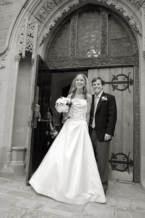 Full length black & white shot of the bride and groom standing outside the church.