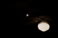 The Full Flower Moon seen through a window reflecting a ceiling fan and light.