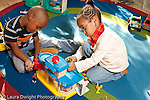 Education preschool 3-4 year olds boy and girl playing with plastic toy airport, human figures, and vehicles horizontal playing separately