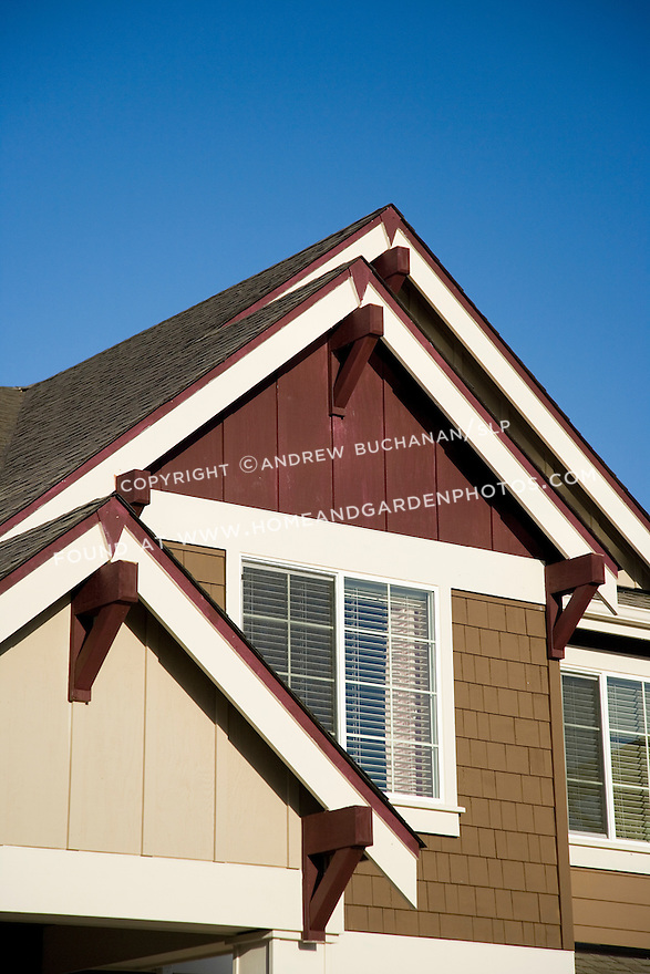 A detail image of Craftsman-style roof peaks painted tan, brown, and maroon reaching skyward in a deep blue morning sky, with plenty of room for text