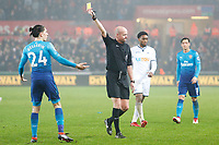Hector Bellerin of Arsenal receives a yellow card from Referee Lee Mason during the Premier League match between Swansea City and Arsenal at the Liberty Stadium, Swansea, Wales, UK. Tuesday 30 January 2018