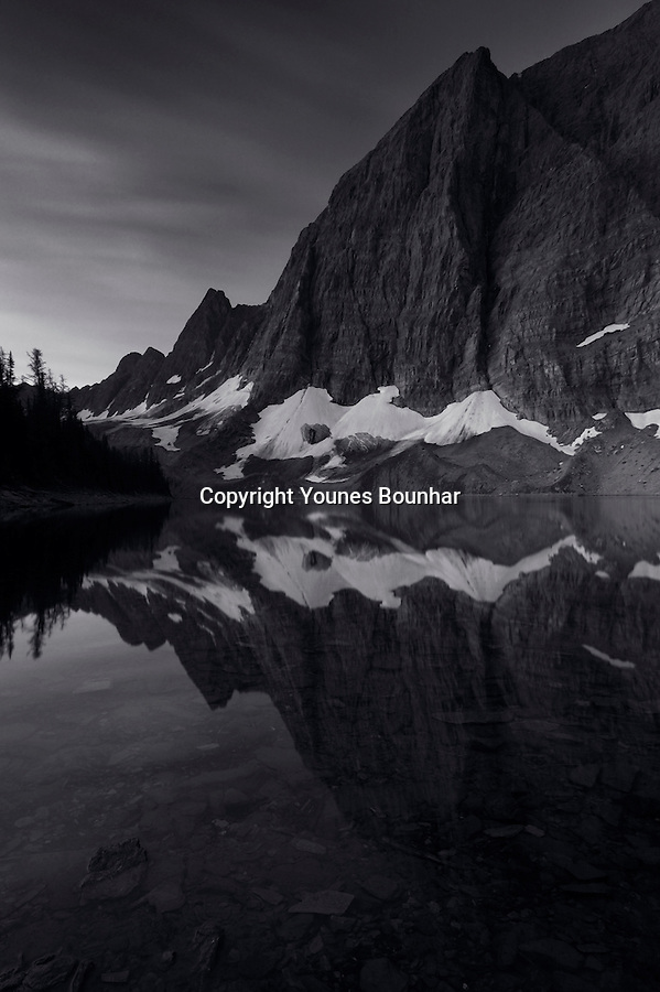 Pre-dawn, twilight reflection of the Rockwall at the surface of Floe lake, Black and White
