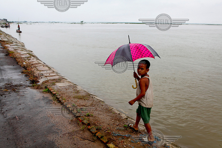Eight year old Sobuj walks with an umbrella along the only path in Sunamganj which isn't submerged under floodwaters during a monsoon.