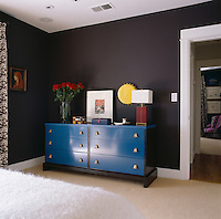 A period blue dresser by designer John Whitticomb sets off the rich chocolate walls of the master bedroom