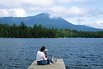 Woman and small boy sitting on a dock, Daicey Pond, Baxter State Park, Maine, USA