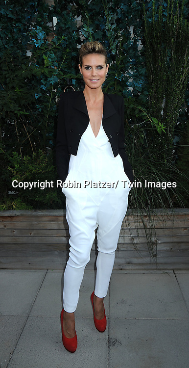 "Heidi Klum, in Givenchy white jumpsuit posing for photographers at The ""Project Runway""  Premiere Party hosted by Marie Claire Magazine on July 28, 2010 at The Empire Hotel Roof in New York City."