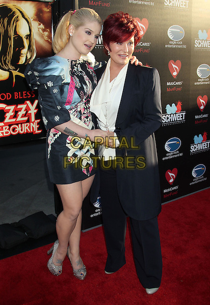Kelly Osbourne & Sharon Osbourne.'God Bless Ozzy Osbourne' Screening To Benefit The Musicares Map Fund held at the ArcLight Cinerama Dome, Hollywood, California, USA..August 22nd, 2011.full length black grey gray pink dress print holding hands tattoo trousers jacket suit white mother mom mum daughter family tattoos.CAP/ADM/RE.©Russ Elliot/AdMedia/Capital Pictures.