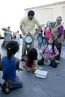 Jamming session with drums between a gypsy girl and a passerby in Kadikoy, Istanbul, Turkey