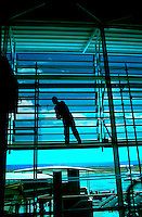 Workman painting window frame in the Reina Sofia airport in the south of Tenerife. Canary Islands, Spain.