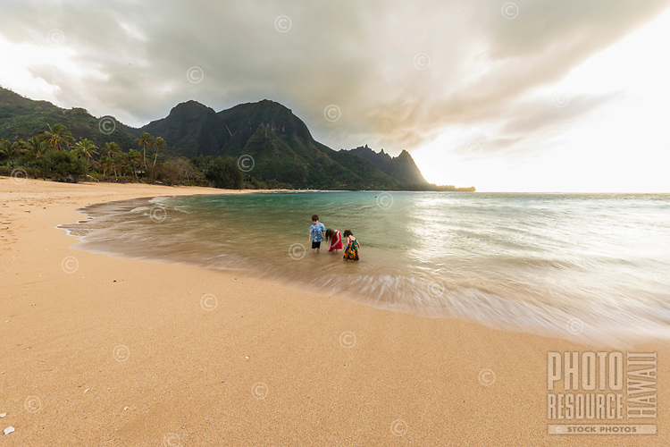 Kids play on the sandbar near sunset at Tunnels Beach, Ha'ena, Kaua'i.