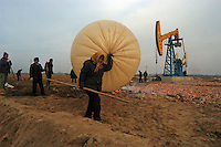 Farmers steal natural gas from the Sinopec Petrochemical oil field in Puyang, Henan province, China in large plastic bags. Farmers in the area often steal natural gas for cooking and heating. They steal the gas from the pipe-line filling a big plastic bag in an hour. As soon as one finishes filling a bag, another family will fill another bag, it goes on continuously. A bag of natural gas is enough fuel for up to one week..