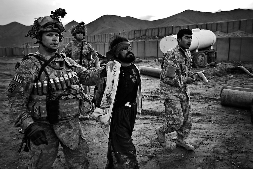 Members of Bravo Company, 1-32 Infantry, 3rd Brigade, 10th Mountain Division detain a suspected Taliban insurgent after an ambush in Charkh (Logar Province), Afghanistan, Sunday, May 3, 2009. Bravo Company is based at the newly established Baugess Forward Operating Base, and frequently engage in fire fights with the Taliban during patrols. The 10th Mountain Division were the first arrivals of permanant reinforcements for the US military in Afghanistan when they arrived earlier this year.