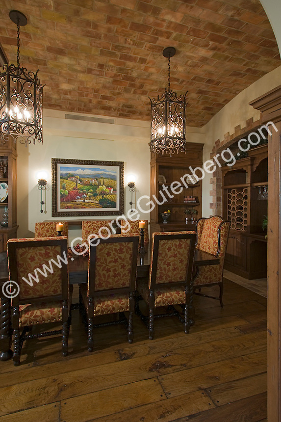 Elegant Spanish-style dining room is seen with wrought iron chandeliers set in vaulted brick ceilings Stock photo of residential dining room
