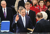 United States President George H.W. Bush is sworn-in as 41st President of the United States by Chief Justice William Rehnquist at the US Capitol on January 20, 1989.  The Speaker of the US House of Representatives Jim Wright (Democrat of Texas) looks on from the left and US Vice President Dan Quayle looks on from the center.<br /> Credit: Arnie Sachs / CNP