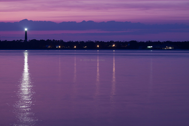 The Pensacola Light reflecting on water as seen  from Fort Pickens at twilight.