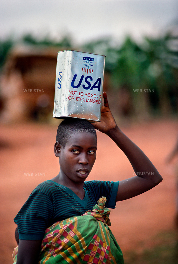 1994. Rwanda. Rotonde Camp. During the Rwandan Genocide, a Burundian Hutu refugee woman holds a can of American food aid. Rwanda. Camp Rotonde. Pendant le génocide au Rwanda, une réfugiée hutue burundaise porte des packs d'aide alimentaire américaine.