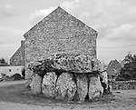 A thousands-year-old dolmen has a house  built snug against it.
