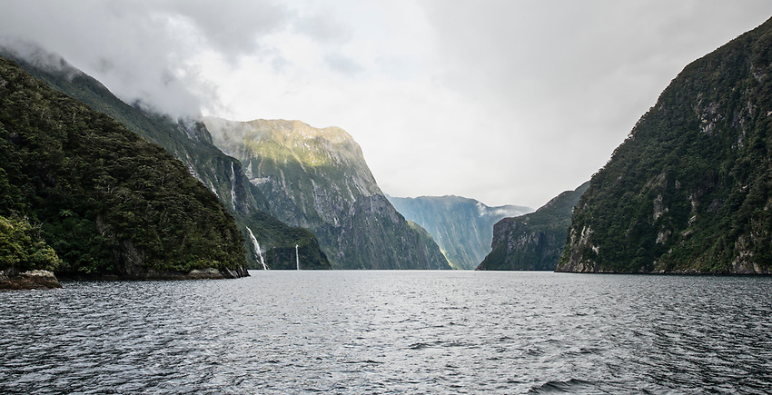 View of Milford Sound from a boat on a cloudy, foggy afternoon