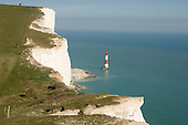 Lighthouse at Beachy Head and walkers on the South Downs Way, East Sussex.