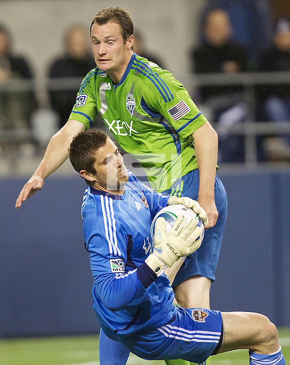 Houston Dynamo goalkeeper Tally Hall crashes to the ground after colliding with Seattle Sounders FC forward Nate Jaqua during play at Qwest Field in Seattle Friday March 25, 2011. The match ended in a 1-1 draw.