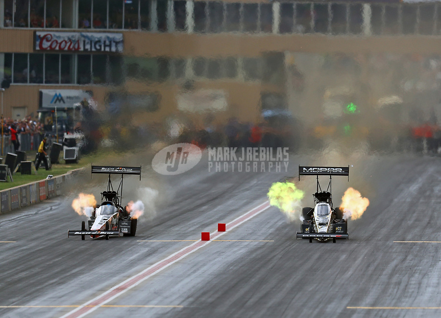 Jul 22, 2018; Morrison, CO, USA; NHRA top fuel driver Clay Millican (left) races alongside Leah Pritchett during qualifying for the Mile High Nationals at Bandimere Speedway. Mandatory Credit: Mark J. Rebilas-USA TODAY Sports
