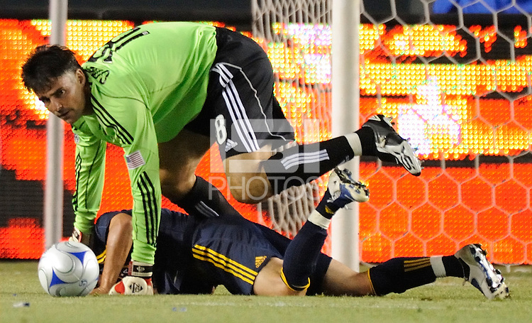 Houston Dynamo's goalie Pat Onstad jumps on the ball as  Los Angeles Galaxy's Bryan Jordan falls in the second half at the Home Depot Center in Carson, CA on Sunday, June 28, 2009..