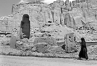 A woman walks past one of the destroyed Buddha statues in Bamiyan, Afghanistan on Tuesday, June 25, 2002. The two Buddha statues are thought to have been carved into the sandstone cliffs of Bamiyan in the third century A.D. At 53 meters (175 feet) and 36 meters (120 feet), the statues were the tallest standing Buddhas in the world.