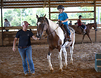 Sarah Markley, a horse trainer and owner of Shelby Farms in Lowell, walks alongside Levi Hodge, 7, of Fayetteville Thursday, June 25, 2020, as he rides around the covered arena during Horse Camp at Lucky Seven Horse Center in Fayetteville. The center partners with Shelby Farms to provide lessons at the camps and will host another camp in July. Visit nwaonline.com/200626Daily/ for today's photo gallery.<br /> (NWA Democrat-Gazette/Andy Shupe)