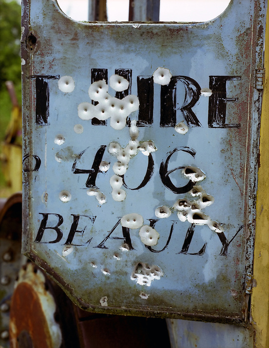 A metal truck cab door peppered with small gauge bullet [pellet] holes . Scotland 2002.