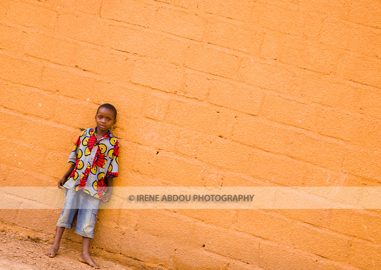 In Ouagadougou, Burkina Faso, a boy stands against an orange wall in the neighborhood of Hamdallaye.