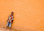 In Ouagadougou, Burkina Faso, a boy stands against an orange wall in the neighborhood of Hamdallaye.
