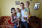"THIS PHOTO IS AVAILABLE AS A PRINT OR FOR PERSONAL USE. CLICK ON ""ADD TO CART"" TO SEE PRICING OPTIONS.   Feride Ramadan Mehmed (left) and her husband Mehmed hold their children Birdzhan, 1, and Erdzhan, 3, in their house in the Maxsuda neighborhood of Varna, Bulgaria. They are Turkish-speaking Roma, and were violently driven out of one neighborhood by racist gangs. They took refuge in a United Methodist Church for a year before finding this small house to rent."