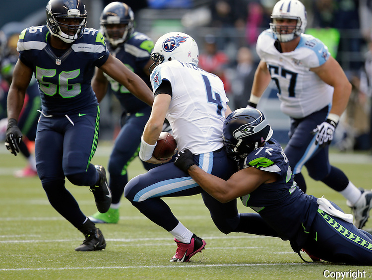 Seattle Seahawks defensive end Michael Bennett , right, sacks Tennessee Titans quarterback Ryan Fitzpatrick (4) in the third quarter at CenturyLink Field in Seattle, Washington on  October13, 2013.  The Seahawks beat the Titians 20-13.   ©2013. Jim Bryant Photo. All Rights Reserved.