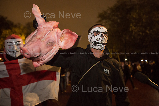 The Mall - The Pig's Head.<br /> <br /> London, 05/11/2015. Thousands of protesters gathered this evening in central London to take part in a demonstration called the &quot;Million Mask March&quot;, which is organised annually by Anonymous, and held globally in more than 400 cities planned to coincide with Guy Fawkes Night (The Gunpowder Plot of 1605). The aim of the demo was to highlight social injustice and Government corruption across the globe, but also to protect the environment, freedom of the internet, oppose mass surveillance and austerity. The rally started in Trafalgar Square, and then the protesters marched on Whitehall, gathering in Parliament Square. Around 7:00pm, a large group marched towards Great George street where clashes erupted with police officers in full riot gears, supported by police dogs and mounted police. Then, the demonstration carried on towards Victoria (where a police car was set on fire), Buckingham Palace and The Mall, to end in the Trafalgar Square area, where the police contained the last activists in &quot;kettles&quot; until around 11:30pm.<br /> <br /> For more information please click here: http://on.fb.me/1mcn5Z7