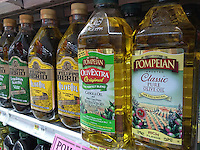 Bottles of imported olive oil and olive oil blends are seen on a supermarket shelf in New York on Monday, March 21, 2016.  (© Richard B. Levine)