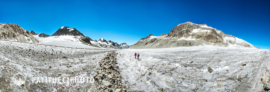 Two hikers in a barren landscape as they walk up the Glacier d'Otemma while on the third day of the Chamonix to Zermatt Glacier Haute Route