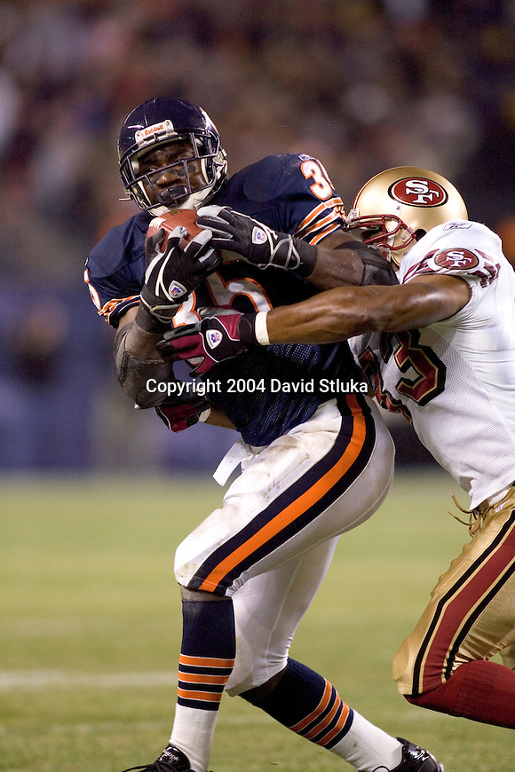 Defensive back Tony Parrish #33 of the San Francisco 49ers tackles running back Anthony Thomas #35 of the Chicago Bears at Soldier Field on October 31, 2004 in Chicago, Illinois. The Bears defeated the Niners 23-13. (Photo by David Stluka)