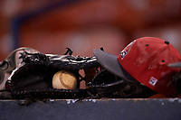 Ball State Cardinals hat, gloves, and baseball on the dugout before a game against the Wisconsin-Milwaukee Panthers on February 26, 2016 at Chain of Lakes Stadium in Winter Haven, Florida.  Ball State defeated Wisconsin-Milwaukee 11-5.  (Mike Janes/Four Seam Images)